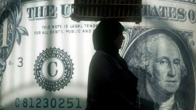 سيدة تسير أمام مكتب للصرافة في العاصمة المصرية