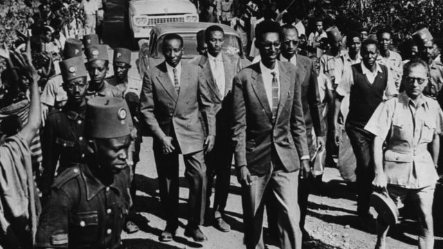 Umwami Kigeli V w'u Rwanda (imbere) akikijwe n'abarinda umutekano n'imbaga y'abaje kumureba igihe yari mu mujyi wa Circa 1959.