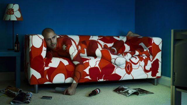 Joven fusionado con el sofá