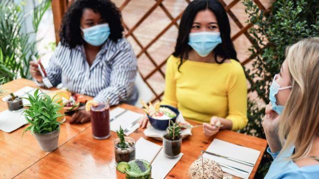 Grupo de mulheres socializando de máscara
