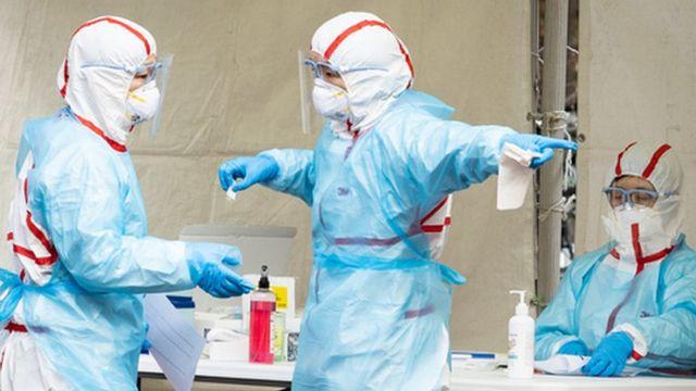 신종 코로나바이러스 감염증(코로나19) 확진자가 1,000명을 돌파한 26일 서울 강동구 명성교회 앞에 마련된 임시 선별진료소에서 관계자들이 분주히 움직이고 있다