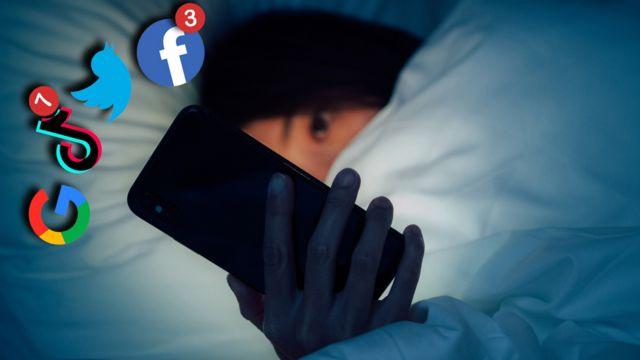 Yatakta Facebook, TikTok, Twitter ve Google logoları ekrandan fırlayan telefona bakan kadın