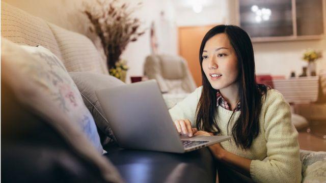 Imagen de una mujer trabajando desde la sala de una vivienda.