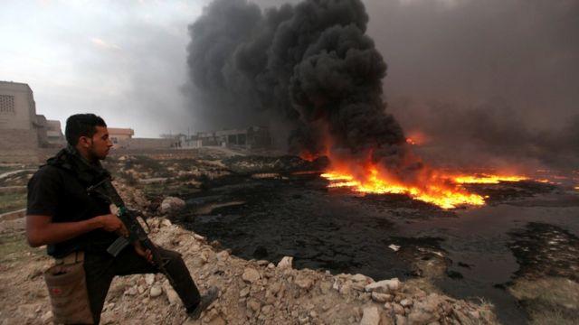 Un miembro de las fuerzas de seguridad observa el fuego y el humo que salen de un pozo petrolero incendiado por miembros de EI en Irak.