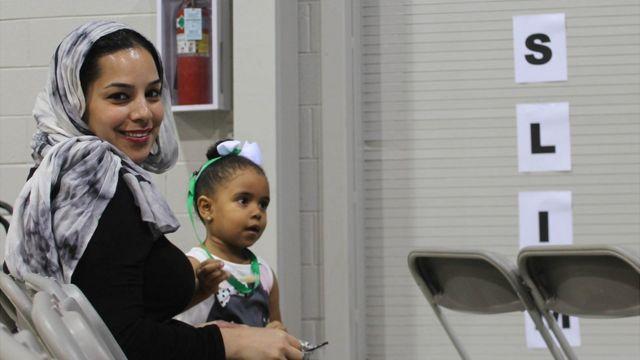 Una mujer musulmana mira a la cámara junto a una niña que está a su lado