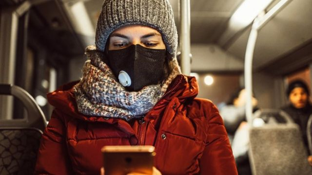 Woman wearing face mask on bus