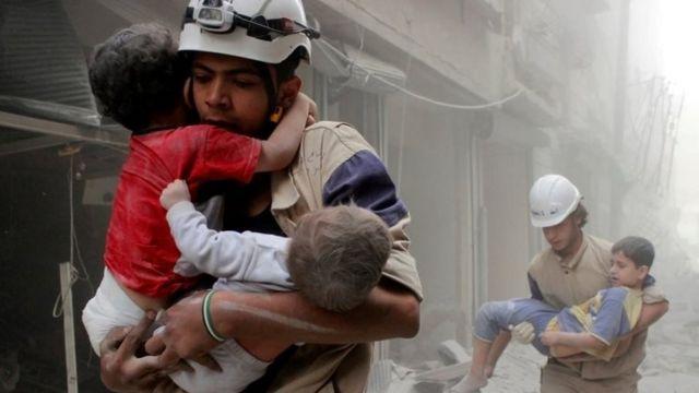 عمال إنقاذ يحملون أطفالا صغارا