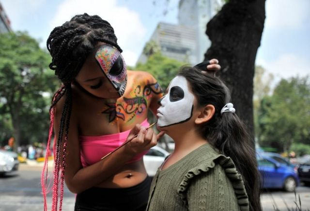 """A girl is made up as Catrina during the """"Catrinas Parade"""" along Reforma Avenue, in Mexico City on October 26, 2019"""