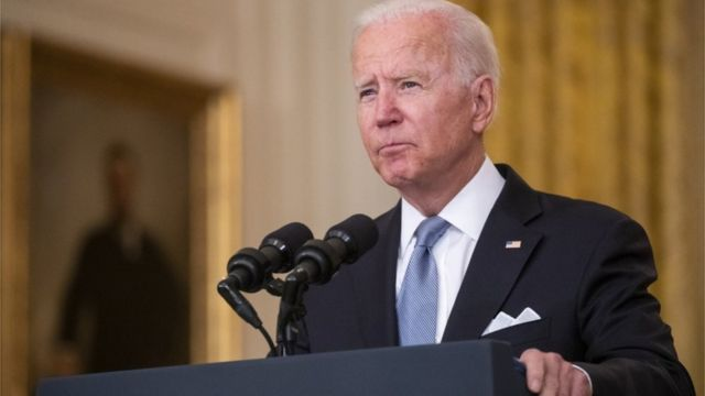 Biden no palanque dentro de sala da Casa Branca