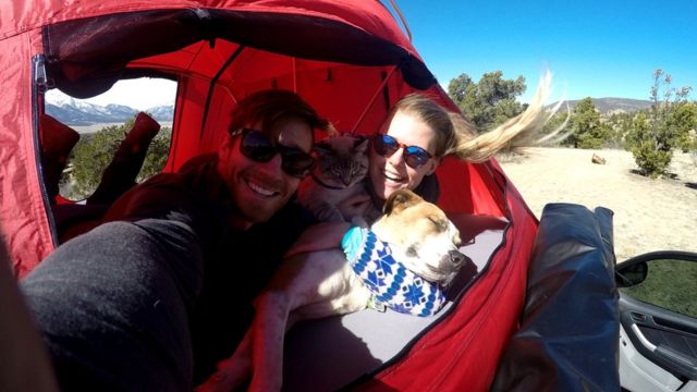 The couple pose for a selfie in a tent with the two animals