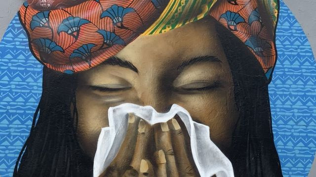 Mural en Senegal con una mujer sonándose.