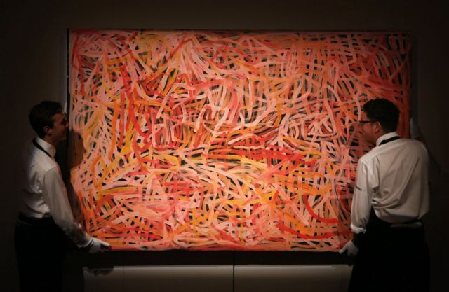 LONDON, ENGLAND - JUNE 04: Sotheby's employees adjust Emily Kame Kngwarreye's 'Wild Yam 2' part of the Aboriginal Art Preview at Sothebys on June 4, 2015 in London, England. The painting forms part of Sotheby's Aboriginal Art Sale which will take place in London on June 10, 2015.