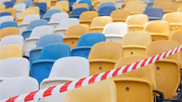 Cadeiras de arquibancada fechadas, com faixa de interdição na frente delas