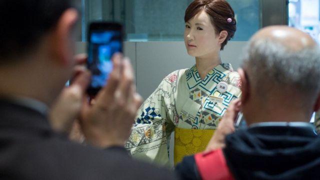 Pessoas fotografam robô humanoide Aiko Chihira na recepção da loja de departamentos Mitsukoshi, em Toquio