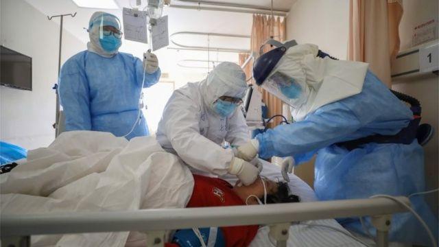 Mulher é atendida por médicos em hospital de Wuhan