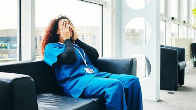 عاملة في مجال الخدمات الصحية تأخذ قسطا من الراحة
