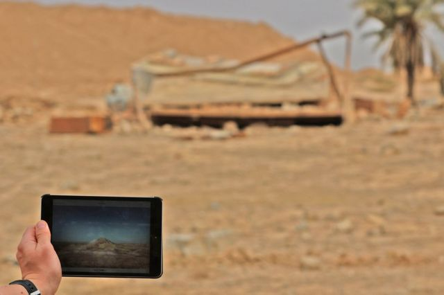 A picture taken on 15 November 2016 shows a tablet with a picture of the ancient ruins of Nimrud before and after their destruction by IS militants
