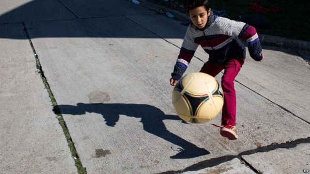 A migrant boy plays with a ball in Austria