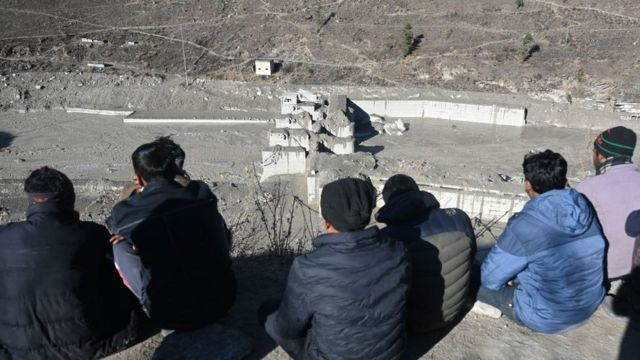 Chamoli disaster survivors observing the remains of a dam