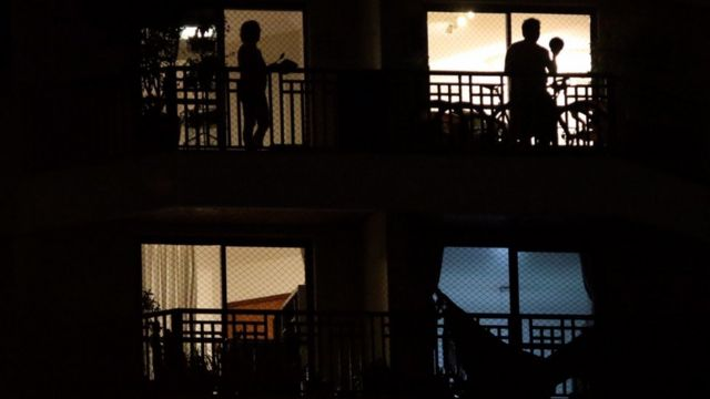 Sombras de duas pessoas em apartamentos diferentes batendo panela da varanda