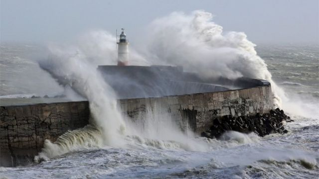 Waves crash over a lighthouse in Newhaven, East Sussex