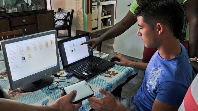 Cubanos reparando computadoras.