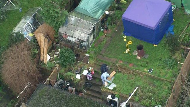 Aerial footage showing person in forensics suit in garden