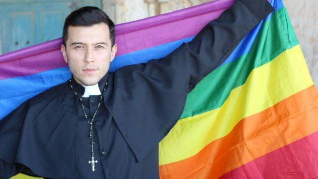 Un sacerdote sostiene una bandera multicolor, símbolo de la comunidad LGBT