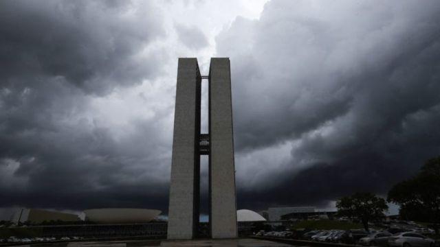 Prédio do Congresso em Brasília sob nuvens carregadas