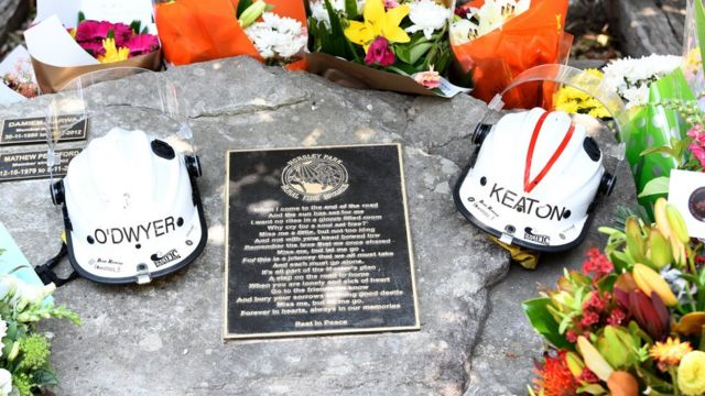 Helmets of Andrew O'Dwyer and Geoffrey Keaton and flowers on their memorial at the Horsley Park fire brigade