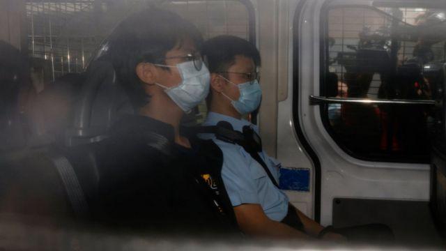 钟翰林(中)由警车押送至香港西九龙裁判法院出庭(29/10/2020)