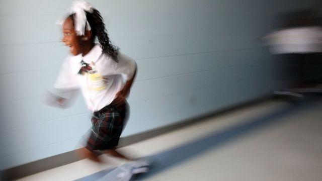 Criança correndo em escola