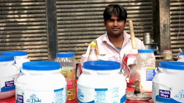 Mohammed Sabir sentado atrás de sua barraca de bebidas a base de iogurte