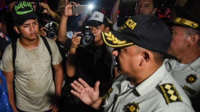 Inmigrantes escuchan hablar a oficila de la policia de Guatemala,