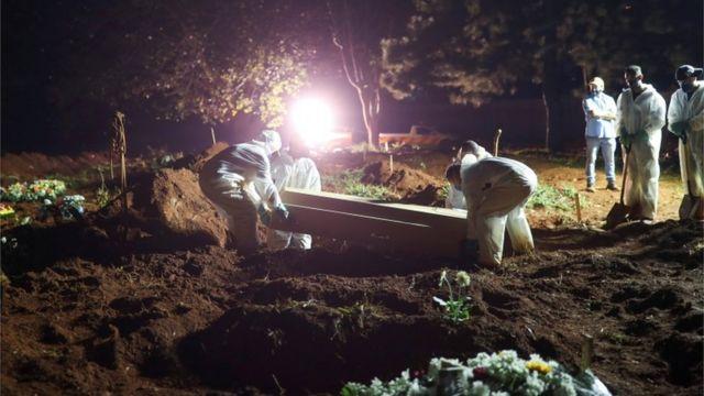 Coveiros vestindo roupas de proteção carregam o caixão de um homem de 32 anos que morreu por covid enquanto holofotes iluminam os túmulos durante os enterros noturnos no cemitério de Vila Formosa em São Paulo, Brasil, 30 de março de 2021
