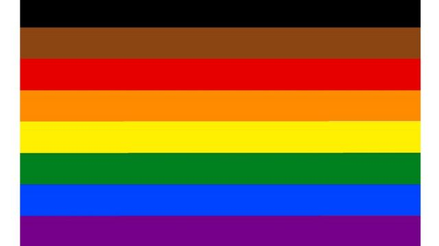 An eight-colour rainbow flag including brown and black for diversity at the top