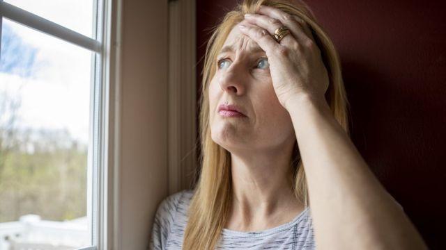 Mulher olhando pela janela durante confinamento