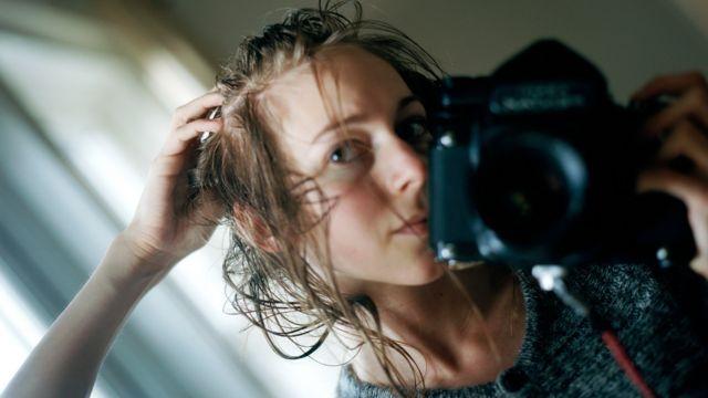 Fotografia de Carly Clarke na frente do espelho quando seu cabelo estava caindo