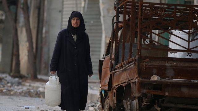 سيدة سورية تبحث عن ماء في حلب القديمة