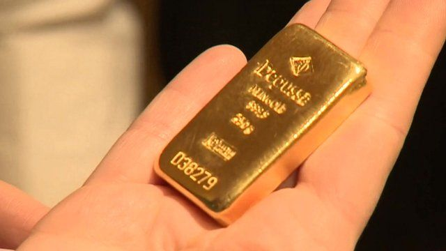 Person holding small gold bar