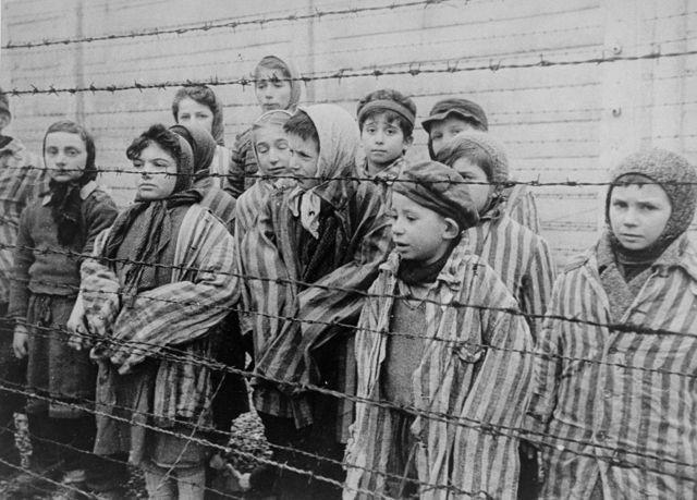 Crianças sobreviventes de Auschwitz, resgatadas pelo Exército da União Soviética, algumas delas identificadas pelo Museu do Holocausto, EUA: 'Tomasz Szwarz; Alicja Gruenbaum; Solomon Rozalin; Gita Sztrauss; Wiera Sadler; Marta Wiess; Boro Eksztein; Josef Rozenwaser; Rafael Szlezinger; Gabriel Nejman; Gugiel Appelbaum; Mark Berkowitz (um gêmeo); Pesa Balter; Rut Muszkies (depois Webber); Miriam Friedman; e as gêmeas Miriam Mozes e Eva Mozes, usando gorros tricotados
