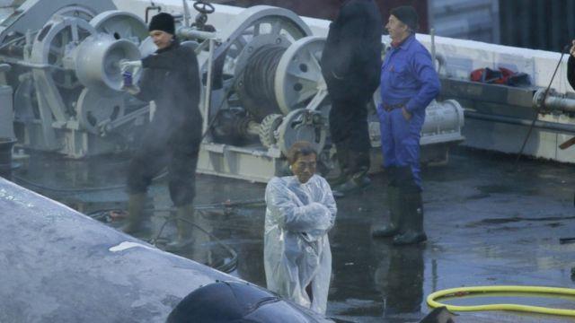 Japon bir denetçi ve gemi mürettebatı balinanın fotoğraflarını çekiyor.