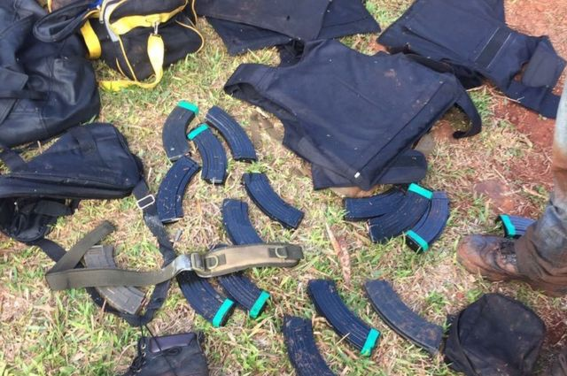 Munições e coletes jogados no chão, num gramado