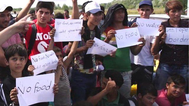 """Migrants at the Hungary-Serbia border hold up signs saying """"no food"""""""