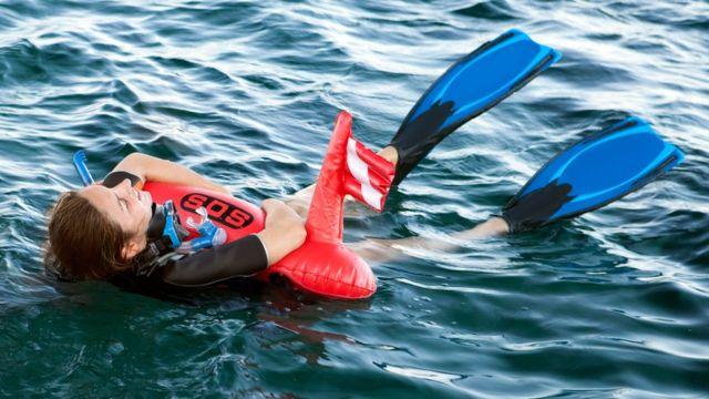 Mulher usa bóia inflável na água