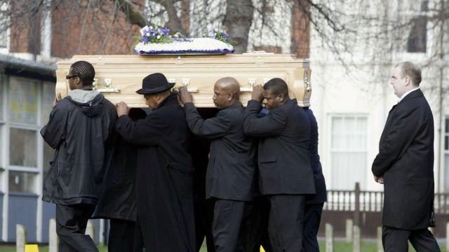 Hombres de luto cargando un ataúd