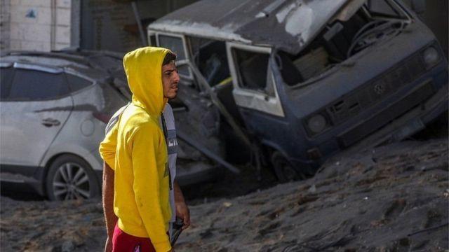 Seorang pria di Gaza di tengah puing mobil dan bangunan yang hancur akibat serangan udara Israel.