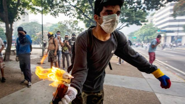 Un manifestante con un cóctel molotov
