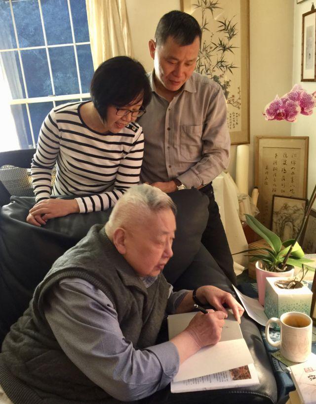 《南方都市报》前总编辑程益中(后)与夫人陈君英(中)在余英时(前)家中观看余教授在书上题字(12/2018)