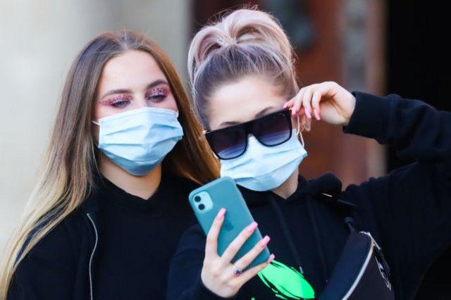 две девушки в масках делают селфи
